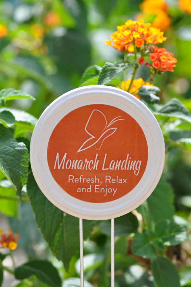 Upcycled masor jar lid painted orange with the words 'Monarch Landing' near lantana.